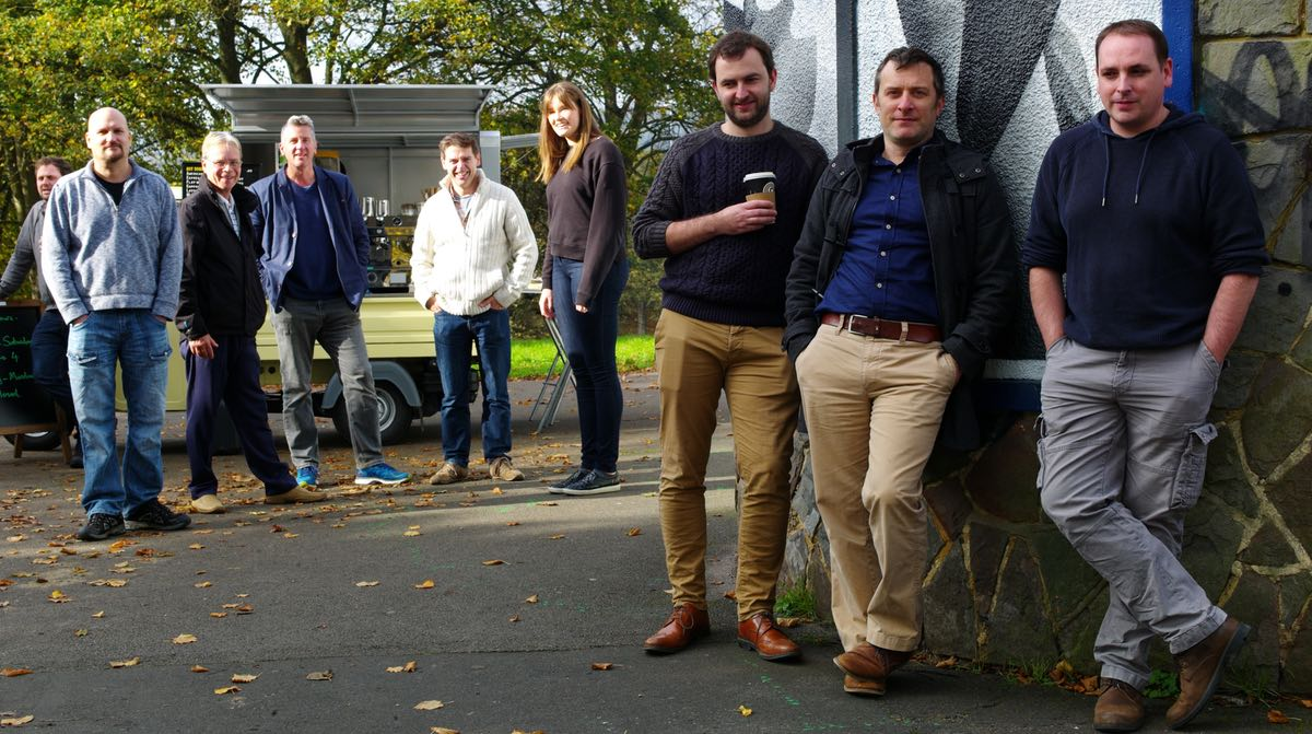 A relaxed group photo of the eight team members of Digital Algorithms against a decorated wall in Greville Smyth Park, Bristol.